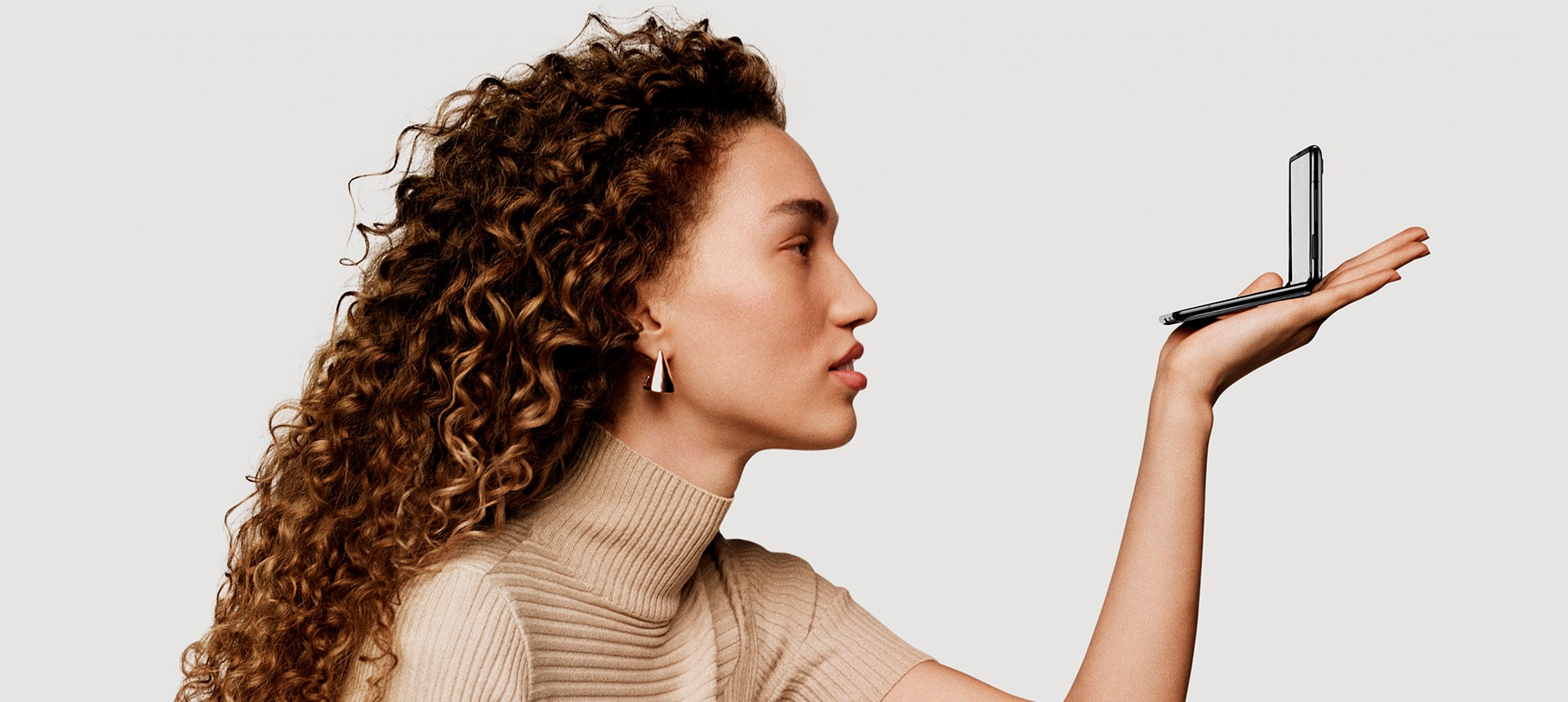 Жінка, що тримає в руці телефон Galaxy Z Flip, складений у вигляді раковини
